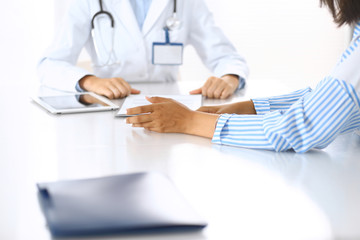 Doctor and patient talking and discussing health treatment while sitting at the desk. Medicine and health care concept