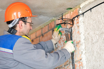 Electrician man construction worker installing fuse box electrical cable at house wall