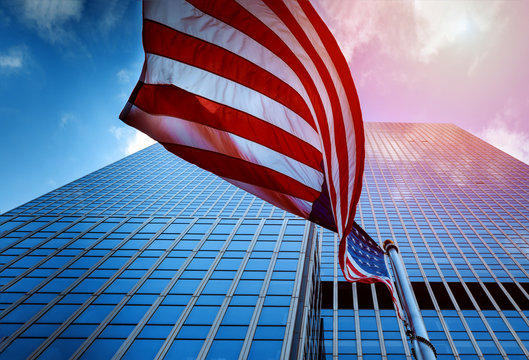 View of the Flag of the United States of America Flying in the a High Rise Glass Tower