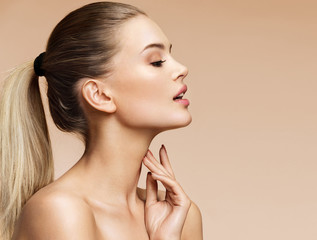 Beautiful girl in profile on beige background. Youth and skin care concept