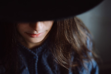 Calm and mysterious portrait of beautiful young  woman wearing  black hat .
