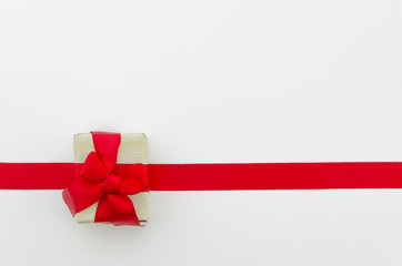 Shiny red satin ribbon and gift box on white background. studio shot. Top view, flat lay, copy space, horisontal