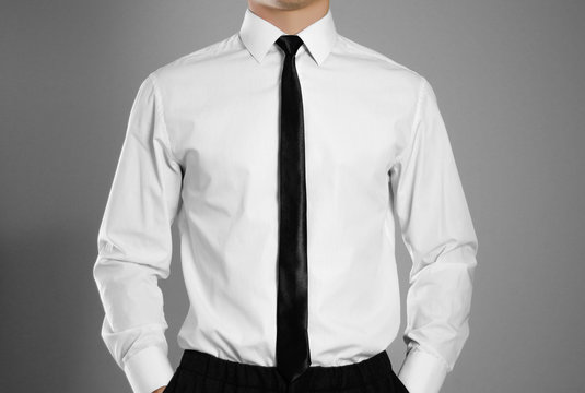 Businessman in a white shirt and tie holding hands in his pockets. Isolated background