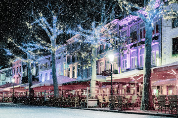 Bars and restaurants with snow and christmas lights on the famous Vrijthof square in Maastricht