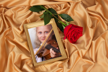 Gold frame for photo and rose on the background of beautiful pleated satin fabric