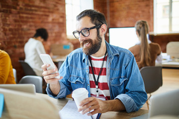 Happy bearded office manager reading message or notificatio or watching video in smartphone while sitting by desk