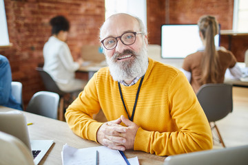 Mature confident head of business company sitting by desk with his working subordinates on background