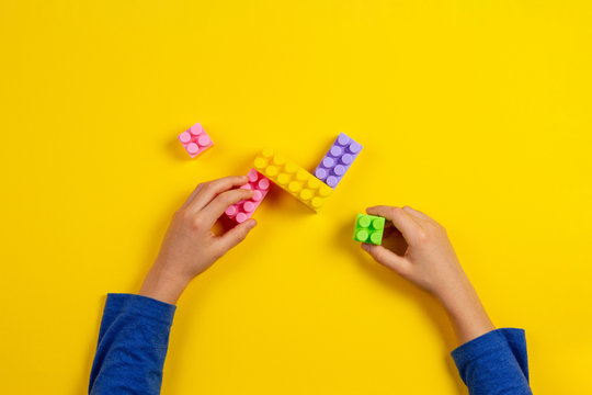 Kid hands playing with colorful plastic bricks on yellow background