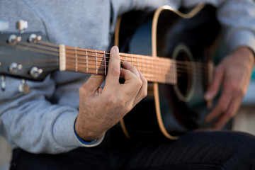 Young man sitting on steps playing guitar and singing, music concept