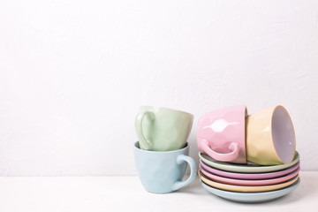 Pile of colourful tea cups and saucers on white textured background.