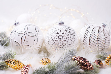 Three white balls, fir tree branches,  brown and golden toys cones  on white fur background.
