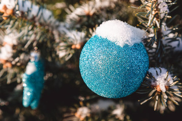 Colorful toys on the christmas tree and snowflakes on the branches and holidays decorations. Blue balls with ornaments of stars and glows. Outdoor christmas trees, decorations in garden