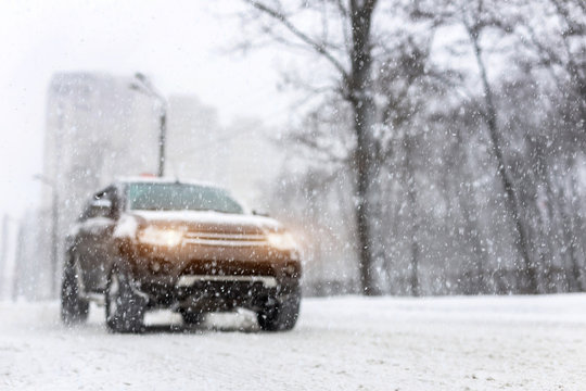 Heavy snowfall and blurred SUV awd car on road. 4wd vehicle on city street at winter. Seasonal roadside assistance concept. Copyspace