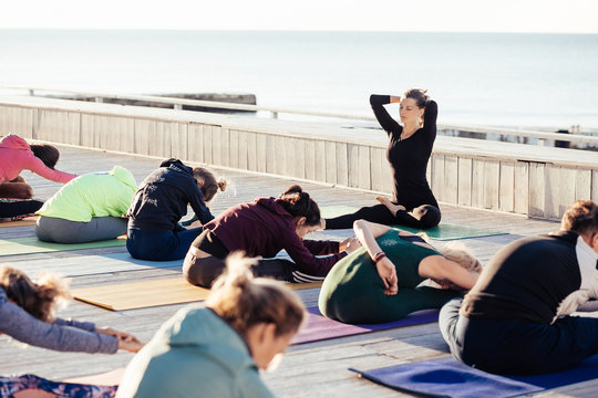 Harmony and calm. Joint yoga classes with healthy and sporty young people along with beautiful yoga teachers outdoors by the sea on wooden fitness terrace. Sunny warm summer morning
