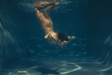 cute sporty girl swims underwater as a free diver in sheer jumpsuit alone
