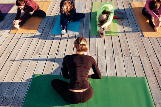 Top view. Young female instructor doing stretching exercises with group of students in the morning on the wooden floor of outdoor fitness terrace. Yoga teacher teaches class. Yoga education. Back view