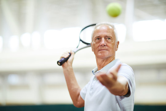 Mature professional player throwing tennis ball and looking at it before hitting with racket