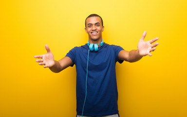African american man with blue t-shirt on yellow background presenting and inviting to come with hand