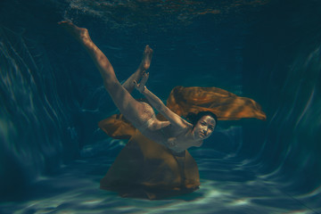 cute sporty girl swims underwater as a free diver in lingerie and mesh catsuit with rhinestones alone