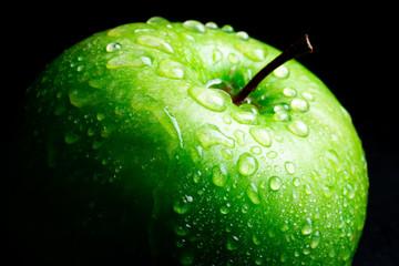 ripe green apple on black background
