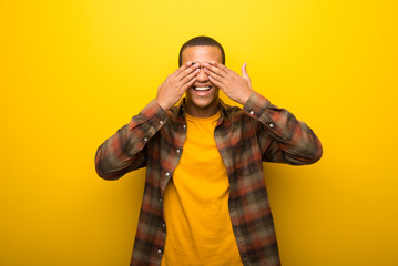 Young african american man on vibrant yellow background covering eyes by hands. Surprised to see what is ahead Wall mural