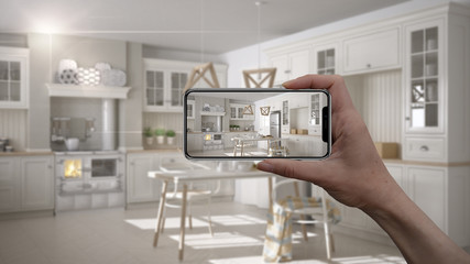 Hand holding smart phone, AR application, simulate furniture and interior design products in real home, architect designer concept, blur background, scandinavian white kitchen
