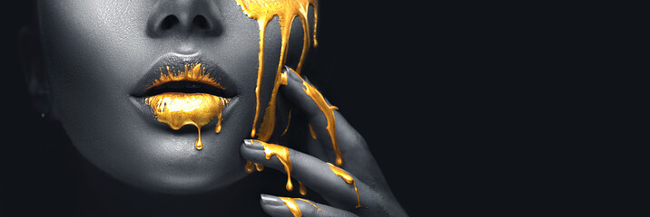 Golden paint smudges drips from the face lips and hand, golden liquid drops on beautiful model...