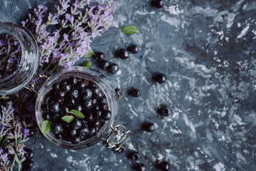 Juicy fresh blueberries on gray concrete background. Picked bilberries in bowl close up. Place for text. Top view