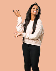 Young afro american woman extending hands to the side for inviting to come on isolated brown background