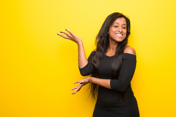 Young afro american woman on vibrant yellow background extending hands to the side for inviting to come