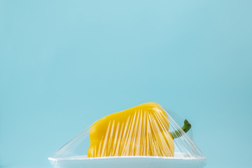 Food in plastic wrap at blue background. Recycling and environment concept: fresh yellow sweet pepper in plastic package.