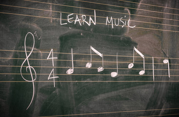 Random music notes written with white chalk on a blackboard. Learn or teach music concepts.