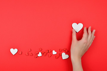 Red and white hearts on a red background. Woman holding white heart. Copy space.