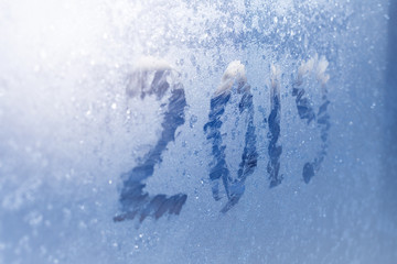 inscription  2019 on a frozen window in hoarfrost. Scratched numbers on blue cold winter background