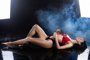 Beautiful sexy wet leggy brunette girl, dressed in black panties and a red bra, sits on the floor and sensually flexes and unties the strings of lingerie in raindrops in theatrical smoke