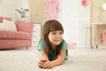 Cute little girl lying on carpet at home