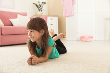 Cute little girl lying on carpet at home. Space for text