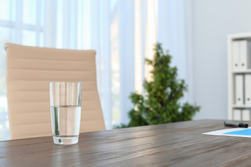 Glass of water on table in office. Space for text
