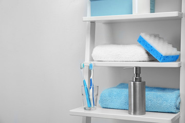 Towels, toiletries and soap dispenser on shelves in bathroom. Space for text