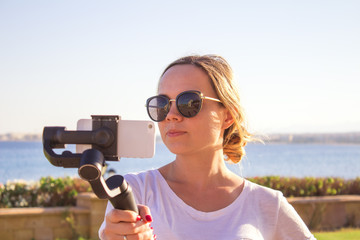 Video blogger girl. Operator with action camera on stabilized grip with gimbal. Happy young woman shoots 4k footage on event outdoor