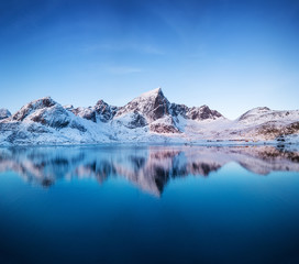 Aerial view at the mountains and reflection on the water surface. Lofoten islands, Norway. Natural landscape during sunrise from air. Drone landscape