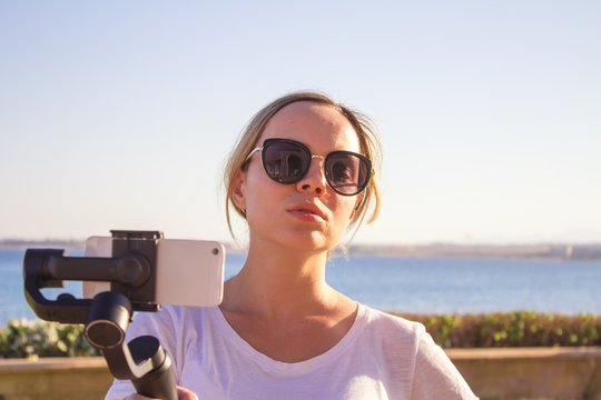 Woman filming sunset on travel, video blogger making video with gimbal and mobile phone, sunset seaside scene