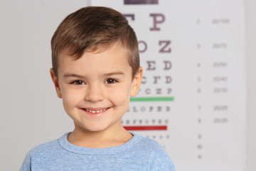 Portrait of cute little boy visiting children's doctor, space for text. Eye examination