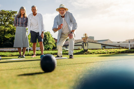 Group of senior people playing boules in a lawn