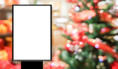mock up blank white poster standing on blur shopping store with christmas decorate background for show or promote promotion