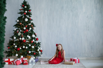 small girl in the red dress at the Christmas tree gifts new year holiday