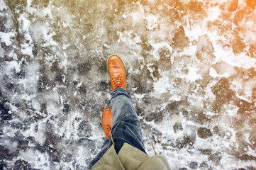 Walk on wet melted ice pavement. First person view on the feet of a man walking along the icy pavement. Pair of shoe on icy road in winter. Abstract empty blank winter weather background