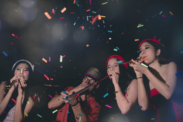 Group of Fun Party People Enjoy with Colorful Confetti in Nightclub while Dancing in Happy Emotion with Friends - Lifestyle on Holiday