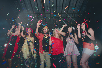 Cheerful Party People Dancing and Throwing Colorful Confetti in Nightclub - Lifestyle on Holiday
