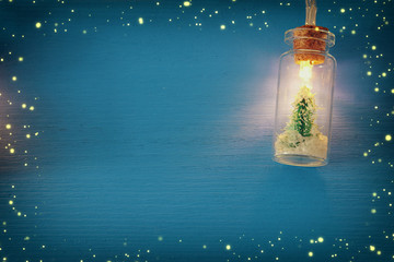 photo of Christmas tree in the masson jar garland light over wooden blue background.
